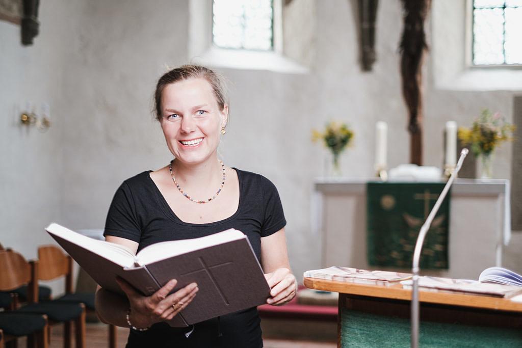 Frau Mahling sitzt in Kirchenbank, mit aufgeschlagener Bibel